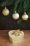 Golden gift box with christmas presents and brunch of xmas tree with golden balls. On wooden background Stock Images