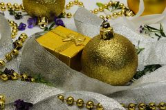 A golden gift box and a Christmas toy shrouded in silver ribbon Stock Image