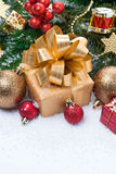 Golden gift box and Christmas tree decorations, vertical Stock Images