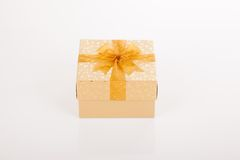 Golden gift box with golden bow on lid Royalty Free Stock Image