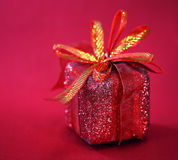 Golden gift box with a red bow Royalty Free Stock Photography