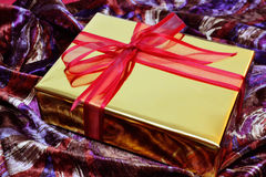 Golden gift box with red bow over colorful velvet Royalty Free Stock Photo