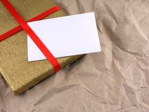 Golden gift box with red bow on vintage old paper Royalty Free Stock Photo