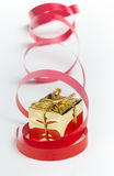 Golden gift box with a red curly ribbon. Stock Photos