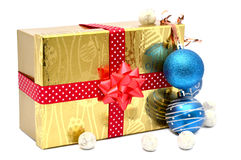 Golden gift box with red ribbon and christmas balls Royalty Free Stock Photography