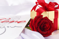 Golden gift box and red roses on white satin background Royalty Free Stock Photography