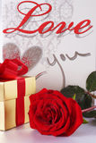 Golden gift box and red roses on white satin background Stock Images