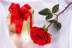 Golden gift box and red roses on white satin background Royalty Free Stock Photo