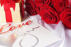 Golden gift box and red roses on white satin background Stock Image