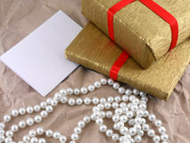 Golden gift box set with red bow with pearls on old paper. Golden gift box with red bow with pearls on old paper Royalty Free Stock Photography