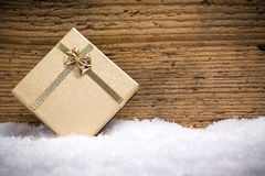 Golden gift box in the snow Royalty Free Stock Image