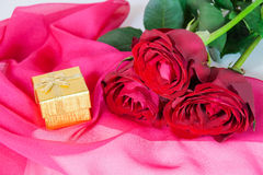 Golden gift box and three red roses on a pink silk scarf Stock Photo