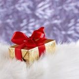 Golden gift box on white fur against blue blurre Stock Photos
