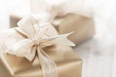 Golden gift boxes with beautiful ribbon and bow on a bright shiny background Stock Photos