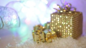 Golden gift boxes with snow and ribbon. Decoration for Christmas winter holidays, present with abstract bokeh shiny stock video footage