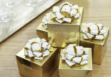 Golden gift boxes with white bows on a wooden table royalty free stock photos