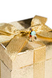 Golden Gift Celebration. Tiny model figures of a romantic couple standing close together on top of a beautiful decorative golden gift box with bow Stock Image