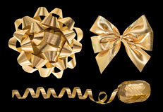 Golden gift decoration objects. Ribbon bow and streamer. Isolated on black background Royalty Free Stock Photography