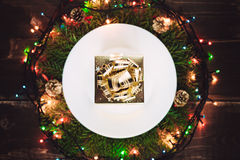 Golden gift on the plate in wreath Stock Images