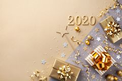 Golden gift or present boxes with golden bows, 2020 number and confetti top view. Christmas and New Year background. Flat lay