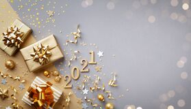 Golden gift or present boxes with golden bows, 2021 number and confetti top view. Christmas and New Year background. Flat lay.