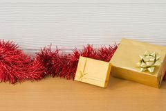 Golden gift with red ribbon on table for New Year. And Christmas concept Royalty Free Stock Images
