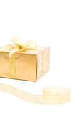 Golden gift and ribbon. Gold gift box with the bow and the ribbon on white Stock Photography