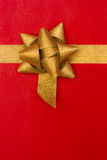 Golden gift ribbon and bow on red background Royalty Free Stock Image