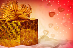 Golden  gift with ribbon and hearts. Stock Images