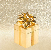 Golden gift with ribbon over shiny background Stock Images