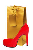 Golden gift shopping bag and red high heeled woman shoe isolated Stock Images