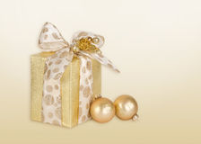 Golden gift wrapped present and Christmas balls Royalty Free Stock Images