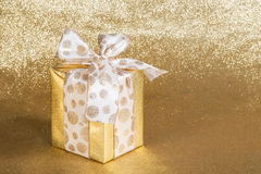 Golden gift wrapped present Stock Image