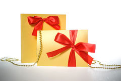 Golden gift wrapped present with red satin ribbon bow on white Royalty Free Stock Image