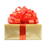 Golden gift wrapped present with red striped bow Royalty Free Stock Photography