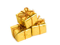 Golden gifts. Three small golden gifts, isolated over white Royalty Free Stock Images