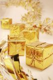 Golden gifts and garland. Row of golden gifts with a gold garland Stock Photo