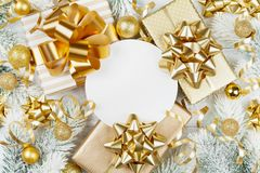 Golden gifts or presents boxes, paper blank, snowy fir tree and christmas decorations on white wooden table top view. Flat lay. stock photo
