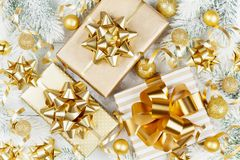 Golden gifts or presents boxes, snowy fir tree and christmas decorations on white table top view. Flat lay. royalty free stock image