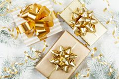 Golden gifts or presents boxes, snowy fir tree and christmas decorations on white wooden table top view. Flat lay. royalty free stock photos