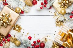 Golden gifts or presents boxes, snowy fir tree and christmas decorations on white wooden table top view. Flat lay. stock photo