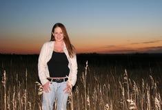 Golden Girl. Girl posing in a field of grain at dusk Royalty Free Stock Image