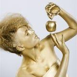 Golden girl with apple. Portrait of girl with golden bodyart posing with golden apple in her hands on gray Stock Image