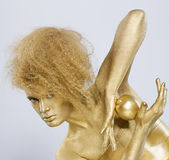 Golden girl with apple. Portrait of girl with golden bodyart posing with golden apple in her hands on gray Stock Photos