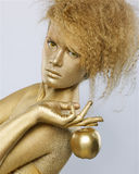 Golden girl with apple. Portrait of girl with golden bodyart posing with golden apple in her hands on gray Royalty Free Stock Photography