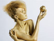 Golden girl with apple. Portrait of girl with golden bodyart posing with golden apple in her hands on gray Stock Photography