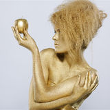 Golden girl with apple Royalty Free Stock Photos