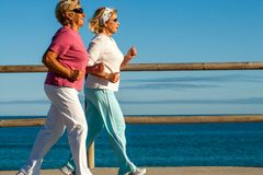 Golden girls jogging along beachfront. Action portrait of elderly women jogging together outdoors Royalty Free Stock Images