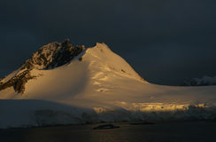 Golden glacier. And mountain sunset, storm clouds in backgroundWilhelmina bayAntarctica Royalty Free Stock Photo