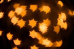 The Golden glare in the form a stars. A festive kaleidoscope, a bright light. Abstract composition of lights and figured bokeh. A good holiday background for royalty free stock photo